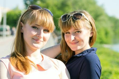 Hübsche Zwillinge Mädchen Spaß an Outdoor-Sommer-Park. Junge Doppel Frauen in der Kamera in der Nähe Fluss suchen Standard-Bild