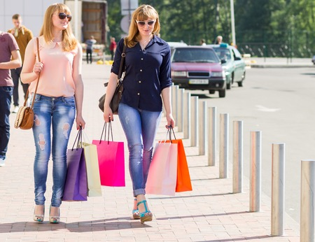 Young smiling pretty women with shopping bags near parking. Twin shopping sisters walking in street at summer day photo