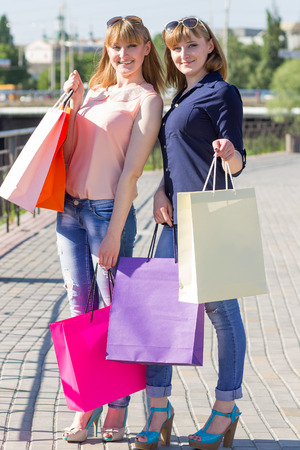 Young twins girls have fun holding their shopping bags. Two women shopping at summer day in city photo