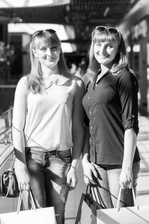 chicas divirtiendose: Gemelos bonitas muchachas que se divierten con las compras en el centro comercial. Imagen en blanco y negro