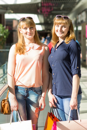 Young twins girls have fun holding their shopping bags. Two caucasian sisters smiling at the shopping mall photo