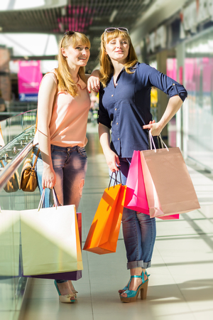 chicas divirtiendose: Gemelos bonitas muchachas que se divierten con las compras en el centro comercial. Las mujeres j�venes con sus bolsas de compras y mirando a otro lado