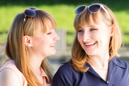 Pretty twins girls having fun at outdoor summer park. Young student sisters laughing talking each other