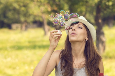 Young pretty caucasian woman having fun with blowing bubbles in summer park. Warm color toned image