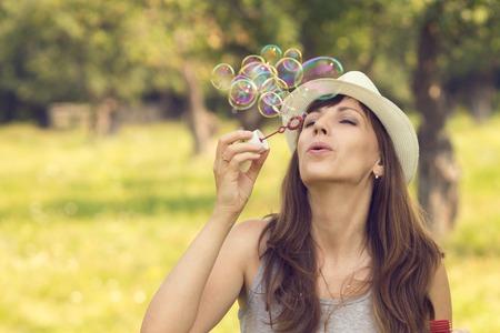 burbujas de jabon: Mujer bonita joven caucásico que se divierte con las burbujas que soplan en el parque de verano. Color cálido imagen de tonos