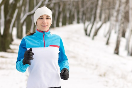 salud y deporte: Mujer joven atleta sonriente trotar en el parque de invierno. Muchacha bonita corriendo en el invierno al aire libre con espacio de copia.
