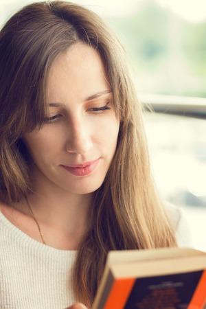 mujer leyendo libro: Hermosa mujer joven que lee un libro en un café cerca de la ventana. Color cálido imagen de tonos