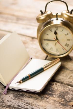 Offene kleines Notizbuch mit Retro-fashioned Füllfederhalter und Wecker hinter. Schreiben Jahrgang Hintergrund
