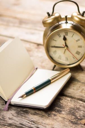 Open small notebook with retro-fashioned fountain pen and alarm clock behind. Writing vintage background