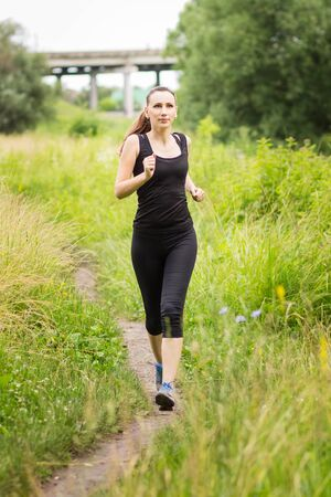 midday: Jogging woman at summer midday. Sport fitness girl make exercises at outdoor
