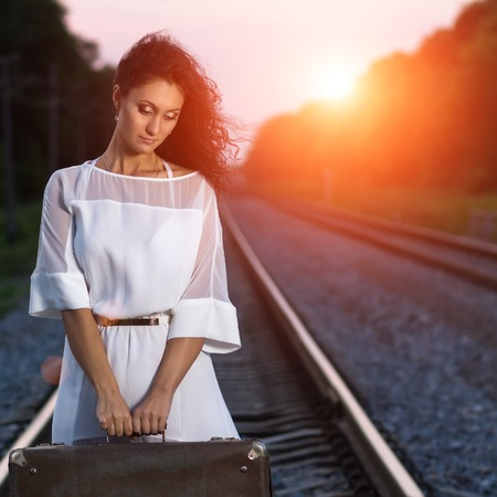 sad lady: Pretty young dreamy woman holding a suitcase at the railway in sunset beams. Traveling background image with copy space Stock Photo