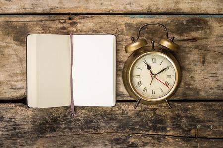 gestion del tiempo: Peque�o cuaderno abierto con el reloj-retro de moda de alarma. Vista superior escritura fondo de la vendimia Foto de archivo