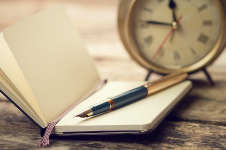 pen and paper: Open small notebook with fountain pen and old-fashioned alarm clock behind. Warm color toned vintage image Stock Photo