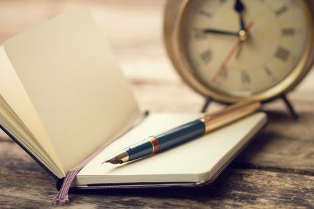 pluma de escribir antigua: pequeño cuaderno abierto con la pluma y el reloj de alarma pasado de moda atrás. color cálido en tonos imagen de la vendimia Foto de archivo