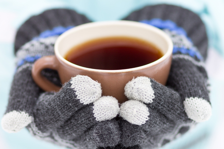 Cup of hot drink in hands. Mug of coffee or tea at winter outdoor activity