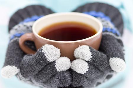 Kop van hete drank in handen. Mok koffie of thee in de winter outdoor activiteit Stockfoto