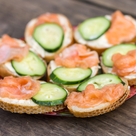 peces: Close up image of sandwiches with salmon and fresh cucmber on wooden background