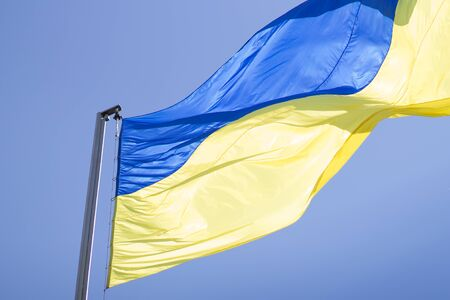 clear day: Blue and yellow national flag of Ukraine waving on blue sky Stock Photo