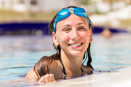 swimming goggles: Young pretty woman having fun in swimming pool. Laughing girl with swimming goggles on summer vacation Stock Photo