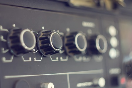 audio equipment: Piece of electrical audio equipment with knobs. Old retro amplifier with selective focus