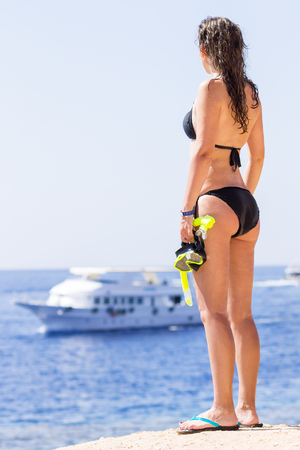 dive trip: Young woman in bikini holding snorkeling equipment looks at the ship on the sea. Slim girl with wet skin looking at the ocean Stock Photo
