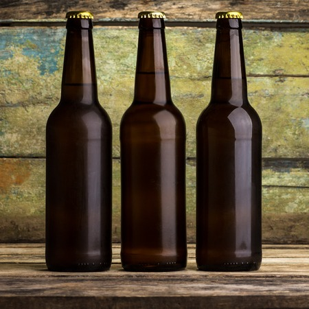 beer bottle: Three bottles of beer against wooden background