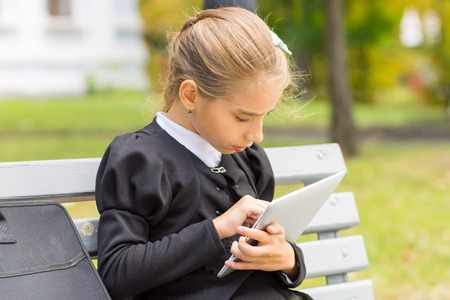 sitting pretty: Little student girl using digital tablet sitting on the bench in park. Stock Photo