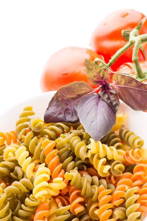 Bowl of raw pasta with basil and tomatoes isolated on white background Stock Photo