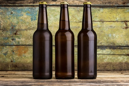 Drie flessen bier tegen houten achtergrond Stockfoto