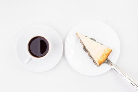Frühstück Restaurant Menü Hintergrund. Keil des Käsekuchens auf dem Spatel und Tasse Kaffee auf weißem Tisch. Draufsicht