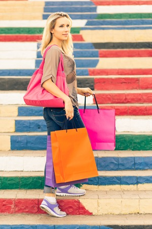 looking aside: Young slim blonde woman holding shopping bags stands on the stairs and looking aside