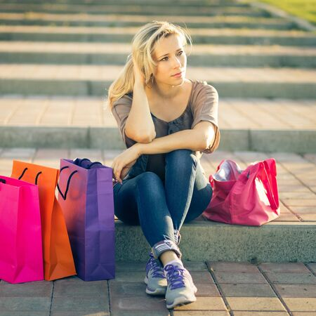store front: Young european woman relax on stairs after shopping. Dreaming adult girl sitting with shopping bags at outdoors street. Toned image