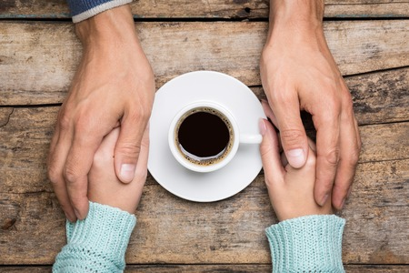 Man holds woman's hand near a cup of coffee top view image on wooden backdrop. Friendship coffee background 스톡 콘텐츠