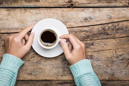 Vrouw handen in sweater het bezit van een kop sterke koffie op houten tafel. Coffee fan bovenaanzicht achtergrond met kopie ruimte Stockfoto