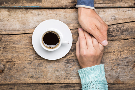 Man holds womans hand with cup of coffee top view image on wooden backdrop. Friendship coffee background