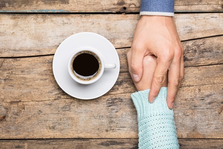 apoyo familiar: Man holds womans hand near a cup of coffee top view image on wooden backdrop. Friendship coffee background
