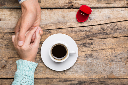 propose: Man holds womans hand and gives a ring in red box for present. Coffee break dating gift