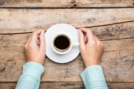 winter break: Woman holding cup of espresso on wooden table. Breakfast cafe menu background