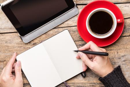 젊은 여자를 작성하거나 태블릿 PC를 사용하여 메모장에 그림과 커피 한잔을 즐기고. 상위 뷰 프리랜서 직장 이미지
