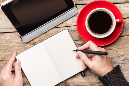 person writing: Young woman writing or drawing into notepad using tablet PC and enjoying cup of coffee. Top view freelancer workplace image