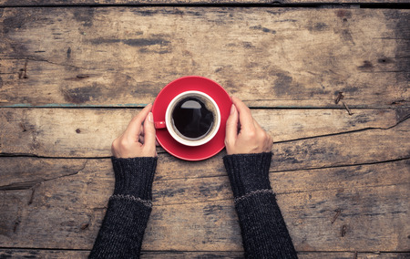 Restaurant or cafe breakfast menu background. Womans hand holding cup of coffee.