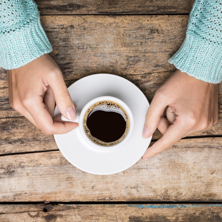 Womans hands holding white small cup of strong coffee. Top view image
