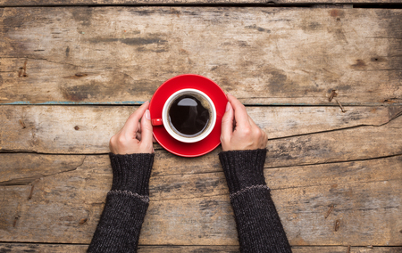 Female hands holding red cup of coffee on wooden background. Top view of morning waking up 스톡 콘텐츠