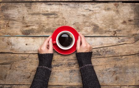 Weibliche Hände halten rote Tasse Kaffee auf hölzernen Hintergrund. Draufsicht des Morgens aufwachen