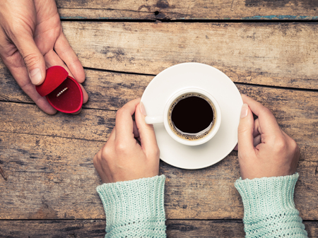 marriage: Woman holds cup of coffee and man gives gold ring as a gift for birthday or engagement Stock Photo