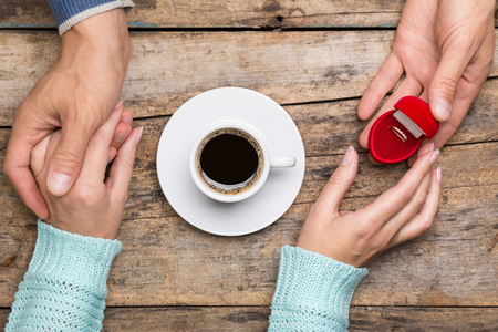 a meeting with a view to marriage: Woman takes gold ring as a gift for birthday or engagement. Top view anniversary image with cup of coffee. Valentines day background