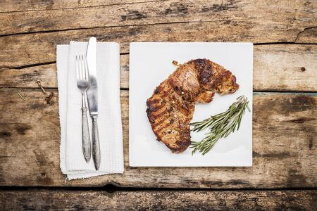 recipe decorated: Grilled beefsteak decorated with rosemary bunch on white plate. Restaurant menu or recipe background. Top view image Stock Photo
