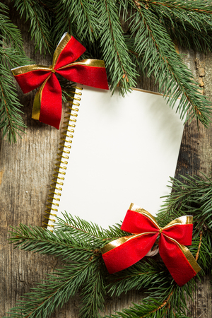 retro vintage: Blank notebook with christmas decoration. Christmas tree branches with red bows and copy space on wooden background. Top view image