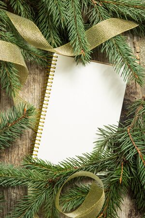 fir tree: Christmas tree branches with blank sheet of notebook and golden ribbon on wooden background. Top view image of cristmas decoration