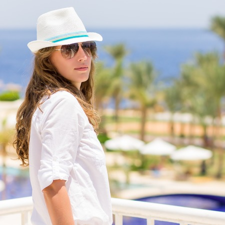 white hat: Young caucasian woman in the tropical resort hotel. Beautiful girl in white hat and shirt with copy space on summer vacation background Stock Photo